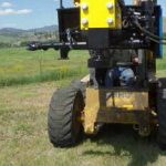 The auger conveniently swings out of the way when driving posts.